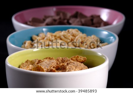 Three colorful bowls with breakfast cereals