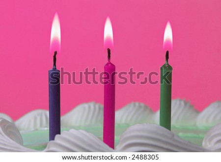 Three colorful candles on a birthday cake. - stock photo