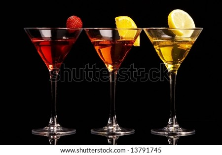 Three colorful cocktails with fruits on black background - stock photo