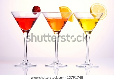 Three colorful cocktails with fruits on white background - stock photo