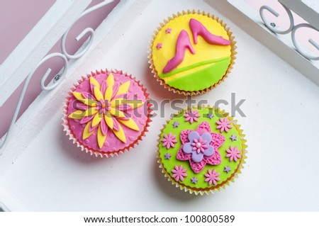 Three colorful cupcakes in pink green and yellow - stock photo