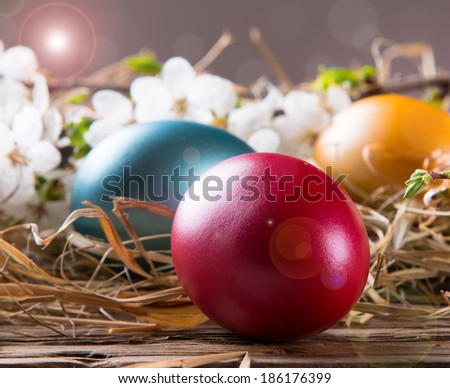 Three colorful easter eggs, brown basket on wooden background with white flower. Spring concept. - stock photo