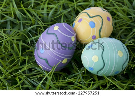 Three colorful Easter eggs hiding in bright green grass.