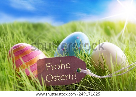 Three Colorful Easter Eggs On Green Grass With Label With German Text Frohe Ostern Means Happy Easter And Sunny Blue Sky - stock photo