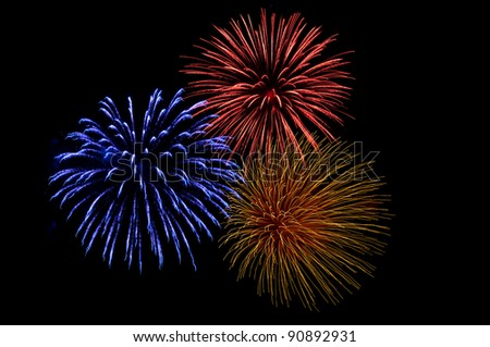 three colorful firework explosions on a black sky - stock photo