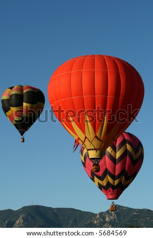 Three colorful hot air balloons during an early morning ascend with the Rocky Mountains as backdrop - stock photo