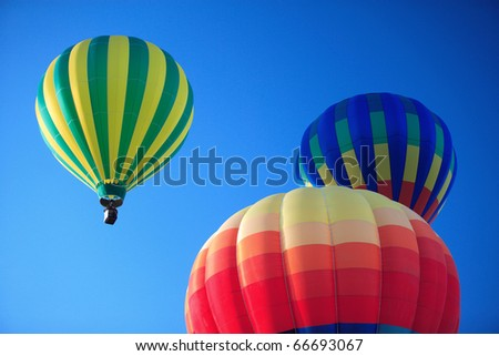 Three colorful hot air balloons rising into a deep blue sky.
