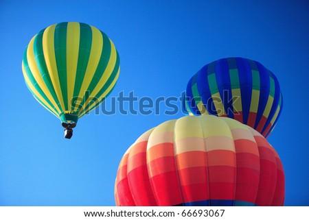 Three colorful hot air balloons rising into a deep blue sky. - stock photo