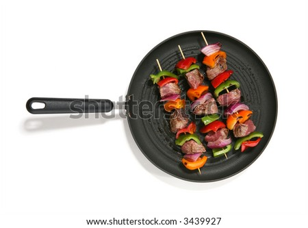 Three colorful kabobs in a grilling in a pan over white