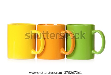 Three colorful mugs for coffee or tea, isolated on white background - stock photo