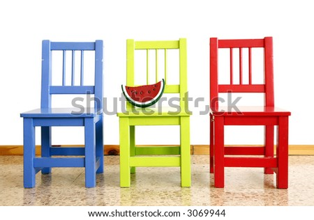 Three colorful nursery chairs with a toy - stock photo