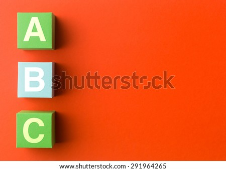 three colorful paper cubes with capital letters, in a row on red background. copy space available - stock photo