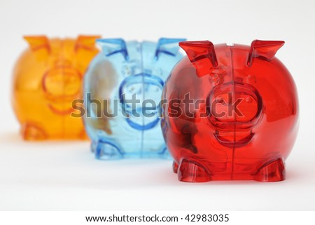 Three colorful piggy banks standing in a row, isolated on white background - stock photo