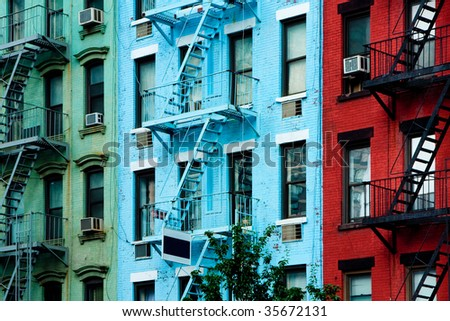 Three colorful, red, blue and green, apartment buildings facades with emergency escapes. Typical New York City, Boston  or Chicago rental complexes with fire escape stairs next to the windows. - stock photo