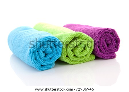 three colorful rolled towels over white background