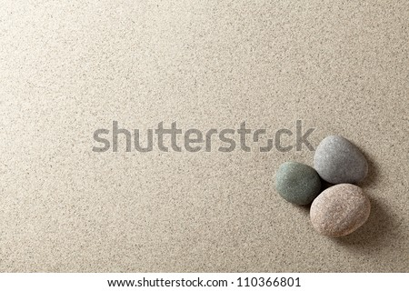 Three colorful round stones on sand background - stock photo