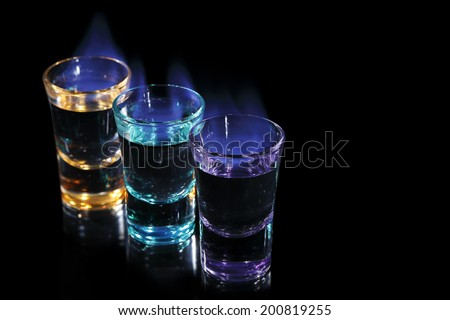three colorful shots on fire on black background - stock photo