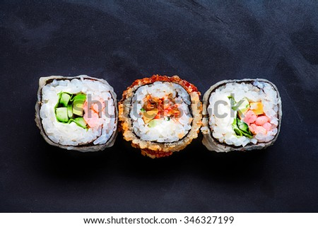 Three colorful sushi on black with copy space - stock photo