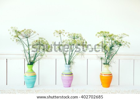 Three colorful vases with flowers arranged on the table - stock photo