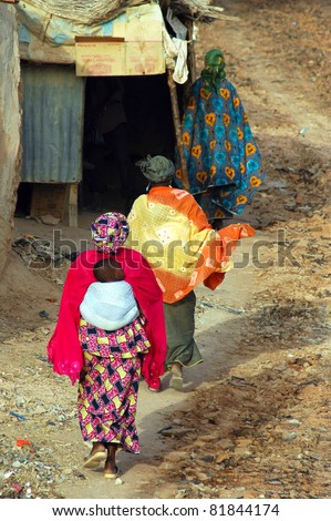 Three colorfully dressed women and a baby walking away from the camera in a town in West Africa - stock photo