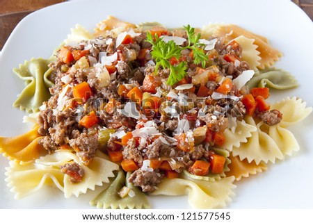 Three colors farfalle pasta with bolognaise sauce garnished with   shaved parmesan cheese.