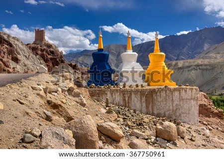 Three colourful buddhist religious stupas at Leh, Ladakh, Jammu and Kashmir, India. Religious symbols in landscape,  with himalayan mountain, road and blue sky. - stock photo