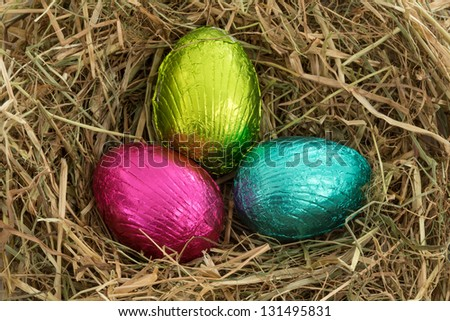 Three colourful easter eggs nestled in straw