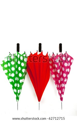 Three Colourful Folded Umbrellas on a White Isolated Background