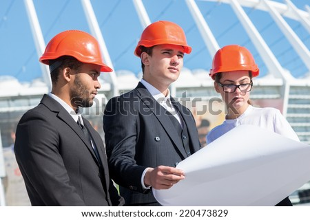 Three confident business architect in protective helmet standing on the site and view the object holding blueprints in hand