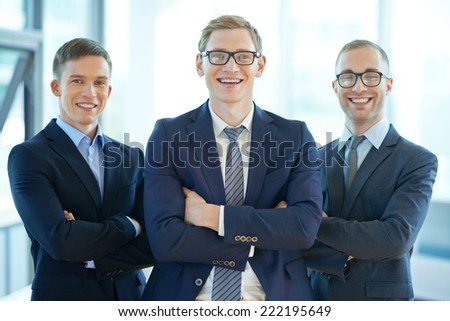 Three confident business workers smiling at camera - stock photo