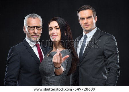 Three confident businesspeople looking at camera and businesswoman gesturing