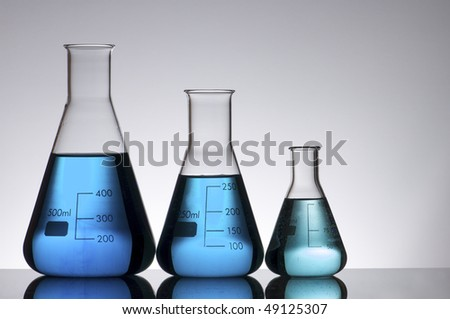 three conical laboratory flask with blue liquid on a white background