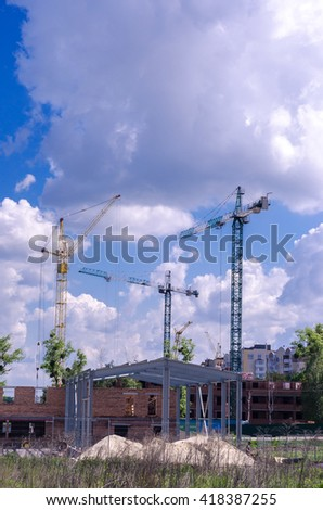 Three construction cranes are building hangar space. Construction work using heavy machinery