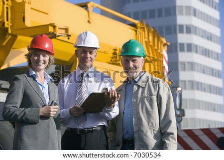 Three construction engineers taking notes and planning in front of a large mobile crane - stock photo