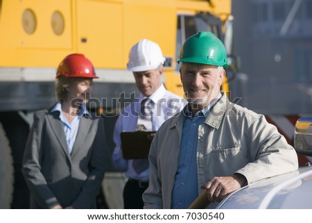 Three construction engineers taking notes and planning in front of a large mobile crane