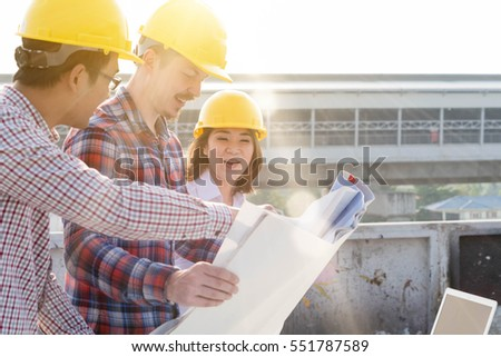 three construction engineers working outdoors in construction site with blueprint