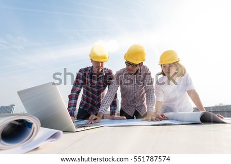 Three construction engineers working outdoors construction stock three construction engineers working outdoors in construction site with blueprint on table malvernweather Gallery