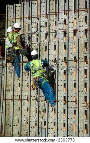 Three construction workers together on a high wall - stock photo