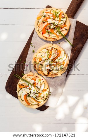 Three cooked delicious mini vegetarian pizzas on a long wooden board standing on a white painted wooden table outdoors in dappled sunlight, overhead view - stock photo