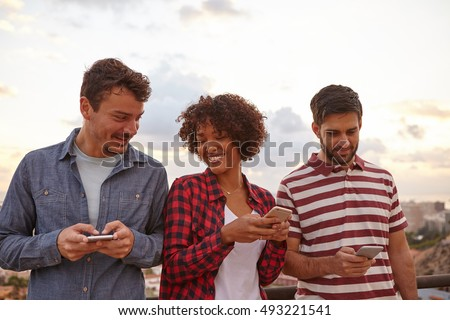 Three cool young friends laughing while looking at their cell phones with a white background, wearing casual clothing