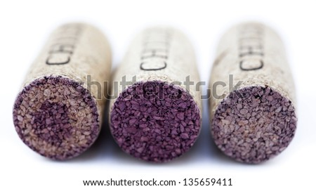 Three corks aligned in a row isolated on white background. Very shallow depth of field. - stock photo