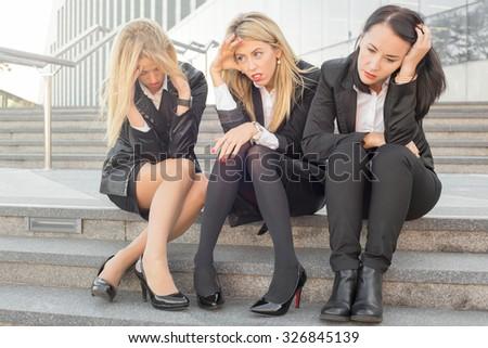 Three corporate business women sitting on stairs  - stock photo