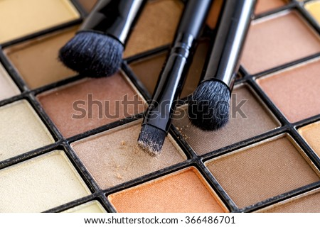 Three cosmetic brushes with light brown eye shadow dust sitting on top of palette of pale nude eye shadow shades - stock photo