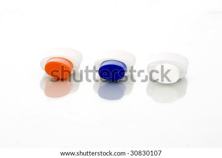 Three cosmetic tubes with colorful covers isolate on a white background