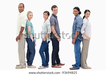 Three couples standing back to back against white background
