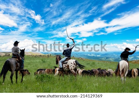 Three cowboys drive herd of horses - stock photo