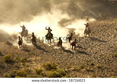 Three Cowboys galloping and roping through the desert - stock photo