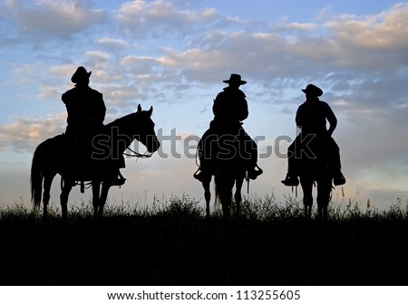 Three cowboys silhouetted against a dawn sky. Montana horse ranch - stock photo