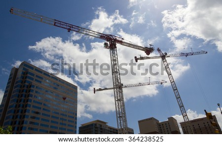 three cranes and four buildings - stock photo
