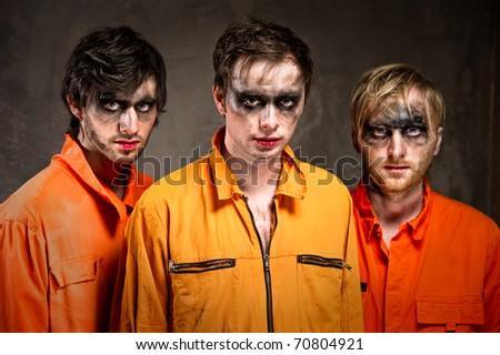 Three criminals in orange uniforms indoors - stock photo